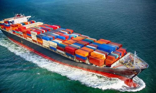 Ein mit Containern beladenes Schiff fährt über das Meer.
