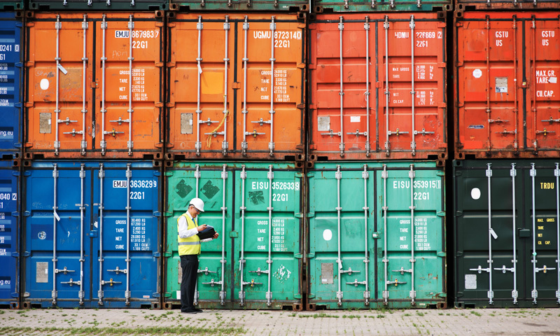 Man with a clipboard standing in front of stacked cargo containers