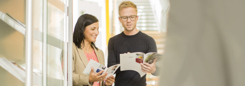 Two people look at informational brochures together