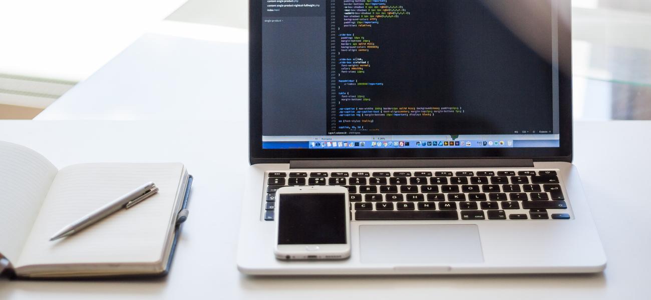 Schreibtisch mit Laptop, Notizbuch und einem Smartphone