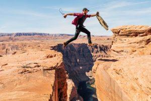 Mann springt über Felsspalte